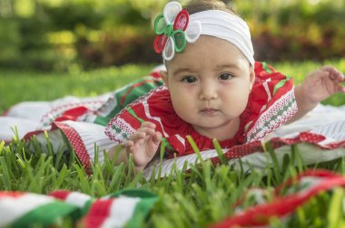 Bebita blanca muy hermosa , sentada en la hierba, con vestido de colores mexicanos, cinta blanca y lazo de colorines en la cabeza. Gesticulando y expresando   emociones diversas, originales y muy simpticas, graciosas, sugerentes. Muy natural y autn