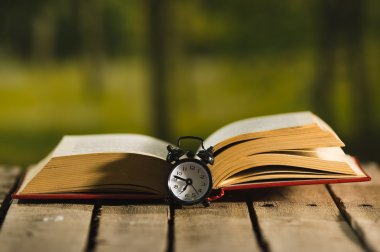Thick book lying open on wooden surface, old fashioned night table clock sitting next to it, magic concept shoot