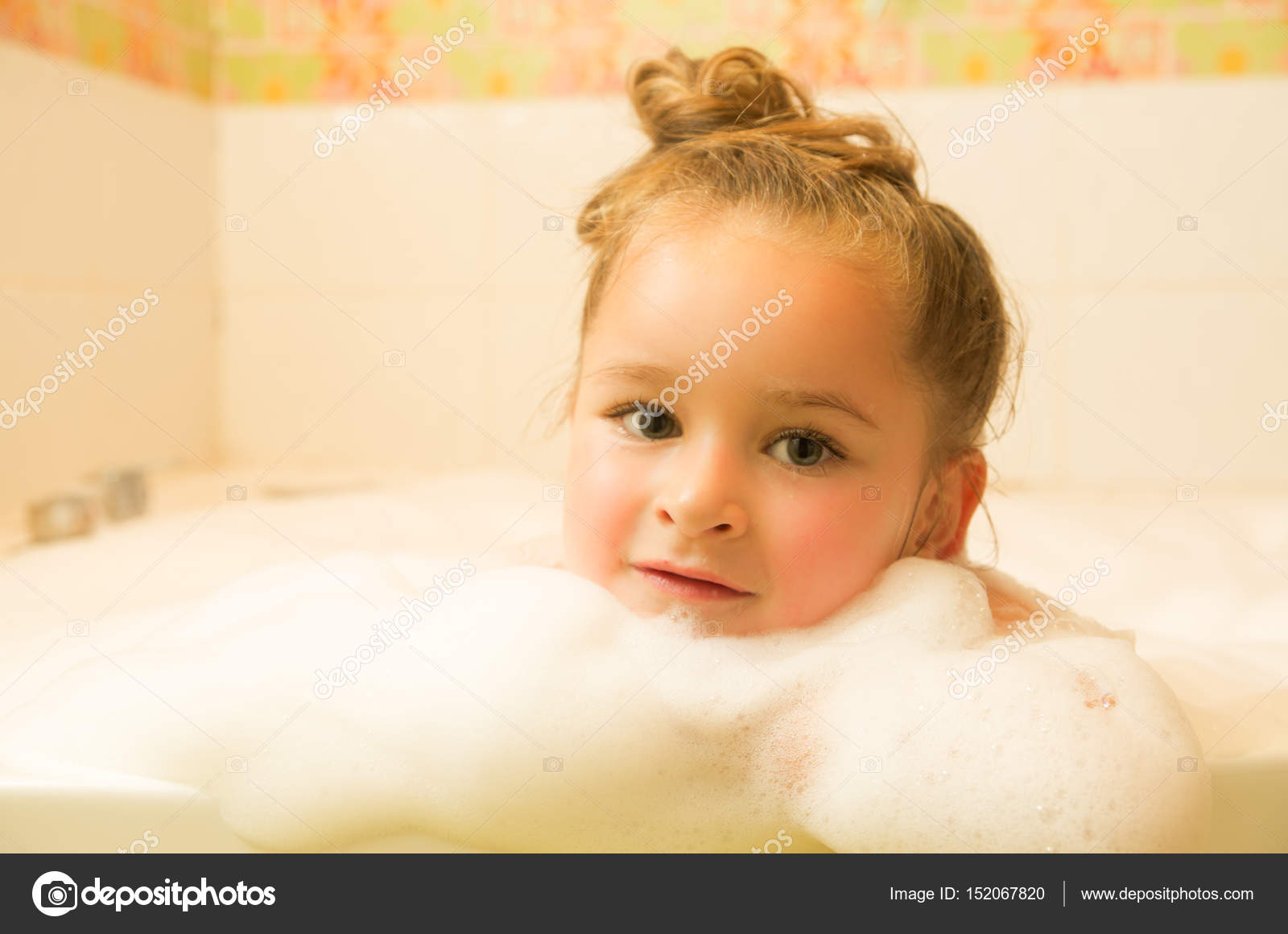 little beautiful girl posing inside of a bathtub with water and foam ...