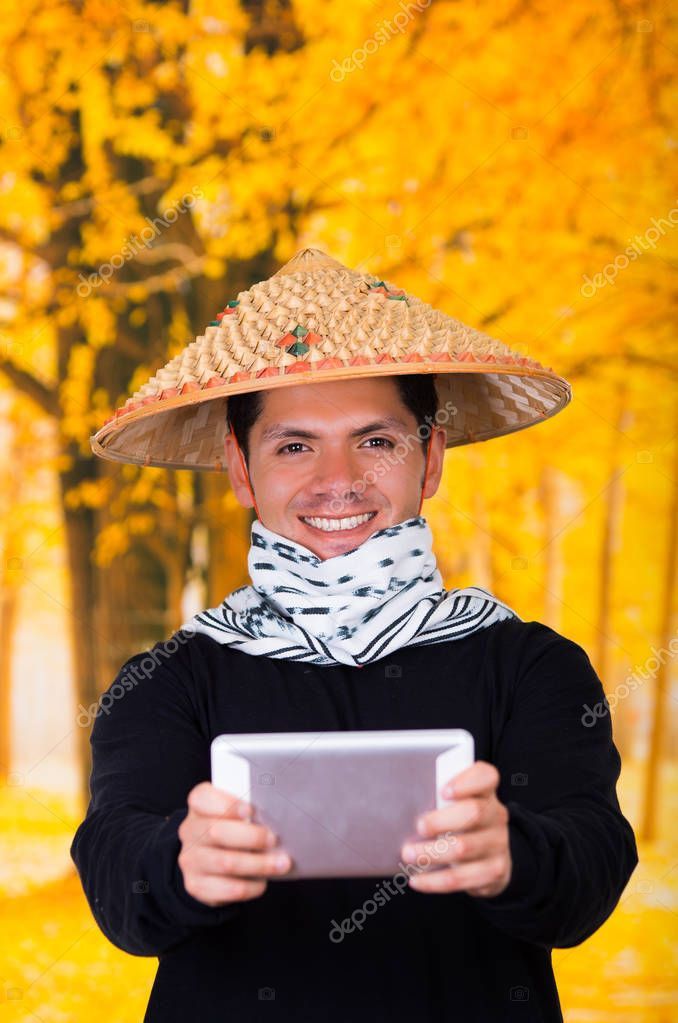 Portrait of a handsome hispanic young business guy wearing an asian conical hat pointing in front of him his Ipad using both hands in autum background