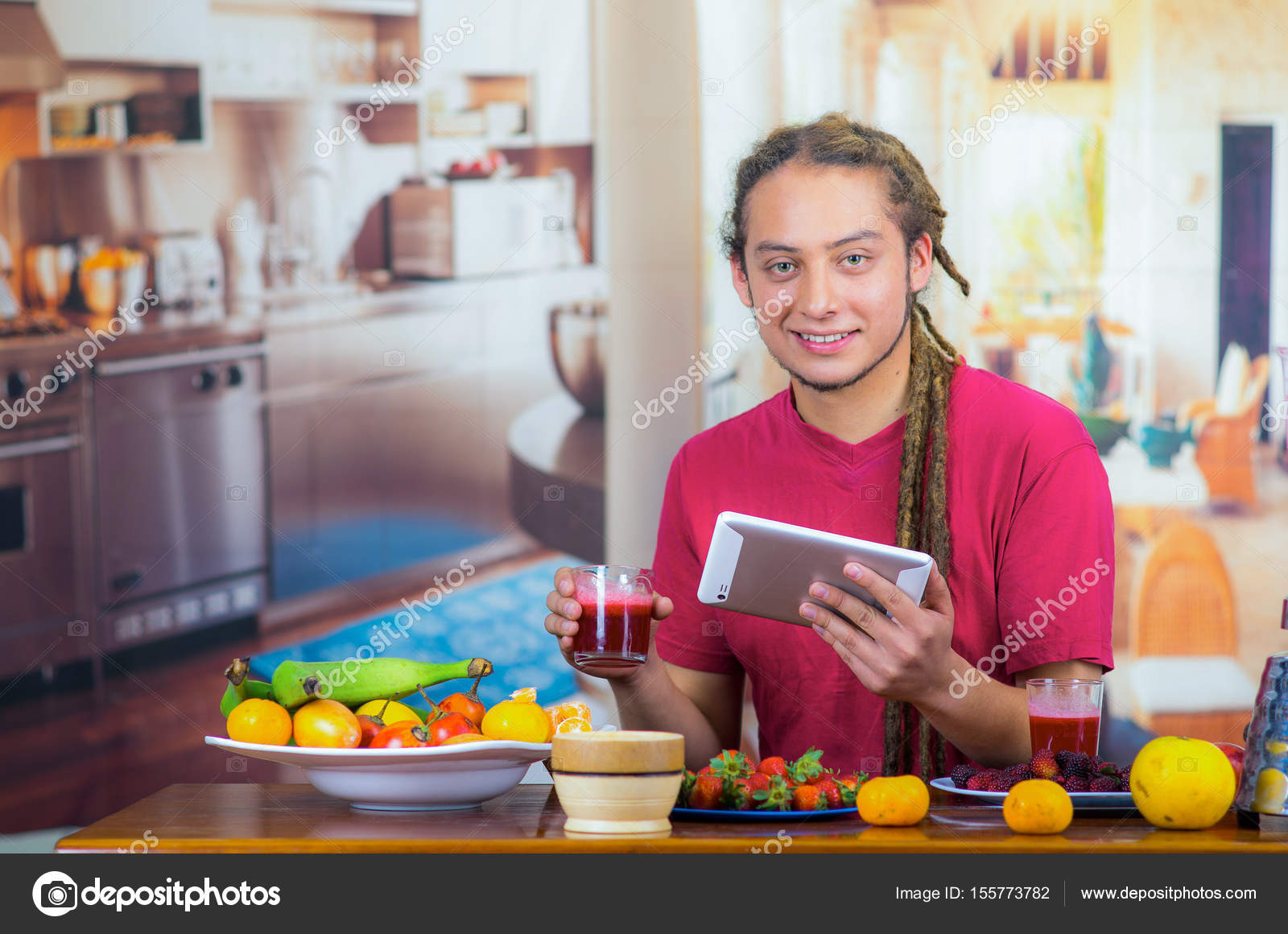 Young man with dreads enjoying healthy breakfast, eating fruits ...
