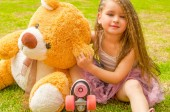 Photo Little girl preschool sitting on backyard next to her teddy bear, wearing her roller skates and crossing her legs, in a grass background