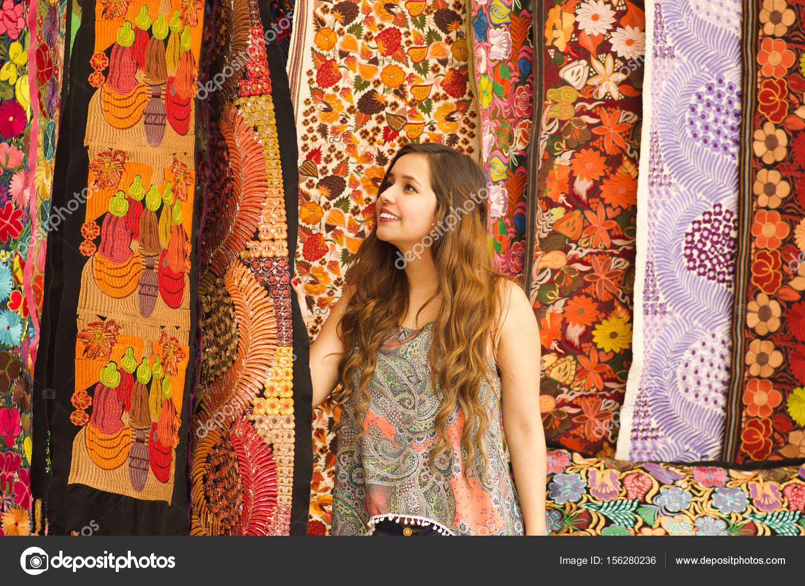 Bella giovane donna sorridente toccare andina tradizionale abbigliamento  tessile filati e tessuti di mano nella priorità bassa dei tessuti lana 2eb5c9221d9