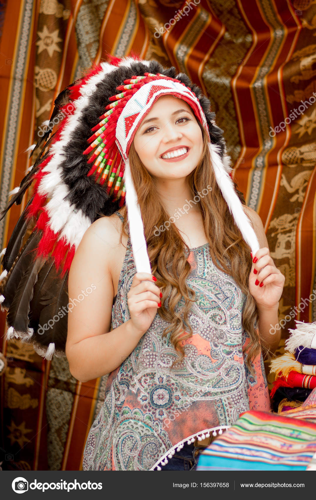 8ba2ec1ea7a A beautiful young woman wearing Native American hat feather. with colorful  fabrics background– stock image