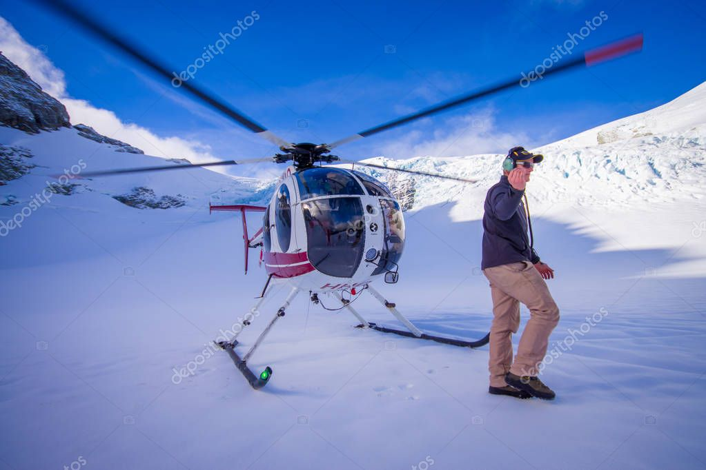 SOUTH ISLAND, NEW ZEALAND- MAY 24, 2017: Close up of helicopter and pilot waiting over the snow for hunters in South Westlands Southern Alps, New Zealand