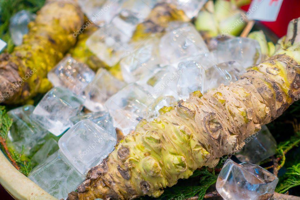 OSAKA, JAPAN - JULY 18, 2017: Fresh wasabi root are sold along the street at Kuromon Ichiba market, Nipponbashi, Osaka, Japan