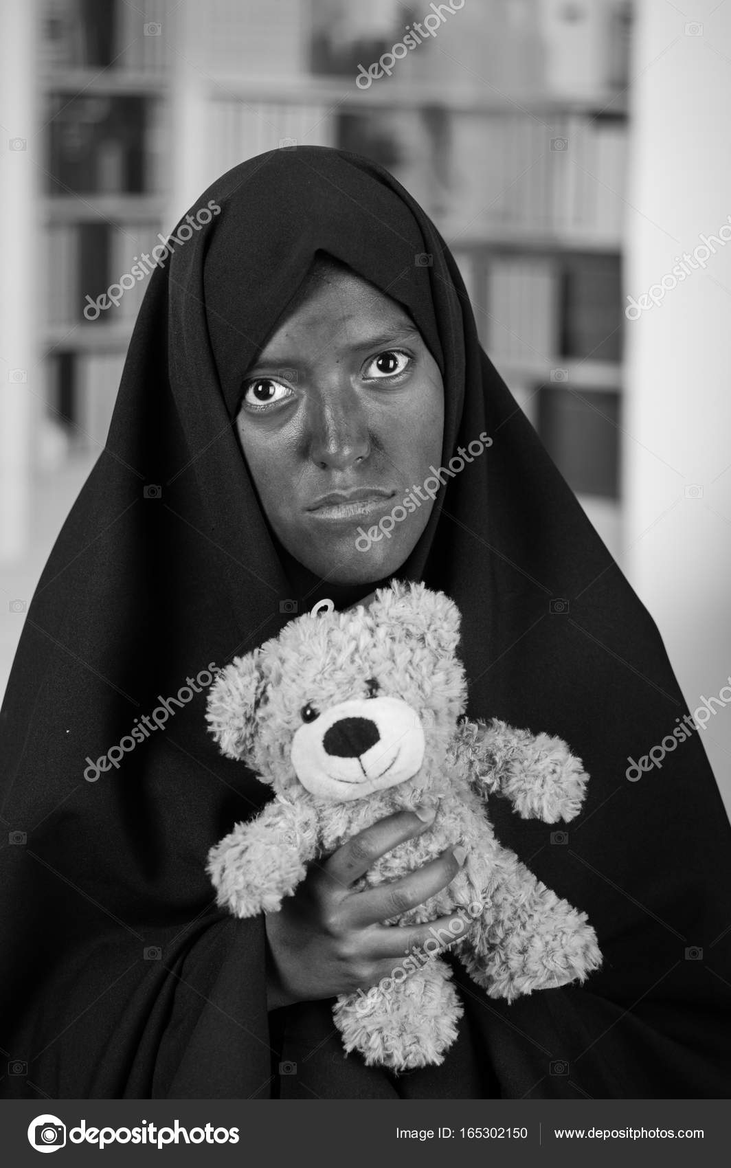 Portrait of a sad muslim girl wearing a hijab and holding her arms her teddy bear in a blurred background in black and white effect