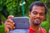 Jaipur, India - September 19, 2017: Portrait of a Indian man holding his cellphone in the hand in Red Fort in Delhi India