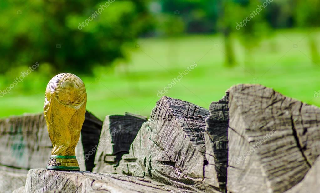 Close up of of fake golden trophy in the form of the globe, over a wooden trunk in the park
