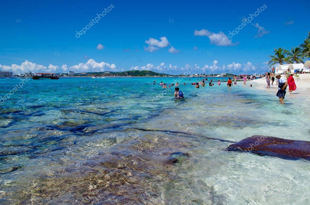 JOHNNY CAY, COLOMBIA - OCTOBER 21, 2017: Unidentified people walking in the beach and enjoying the beautiful sunny day and swimming in the water in the coast of Johnny Cay island with some flags