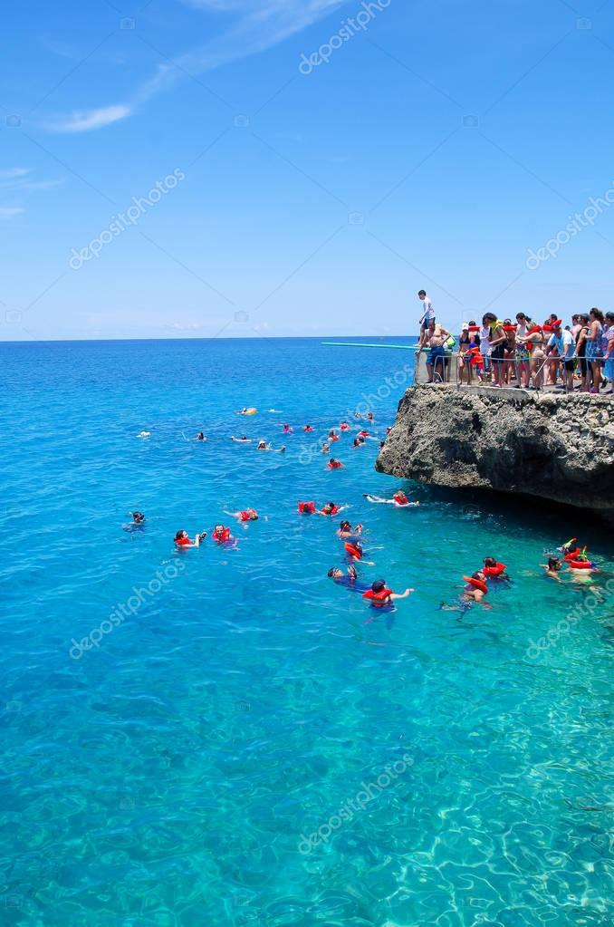 WEST VIEW, COLOMBIA - OCTOBER 03, 2017: Unidentified people jumping from a rock, swimming and enjoying the beautiful view in a gorgeous blue water, San Andres Island from Johnny Cay during a sunny day