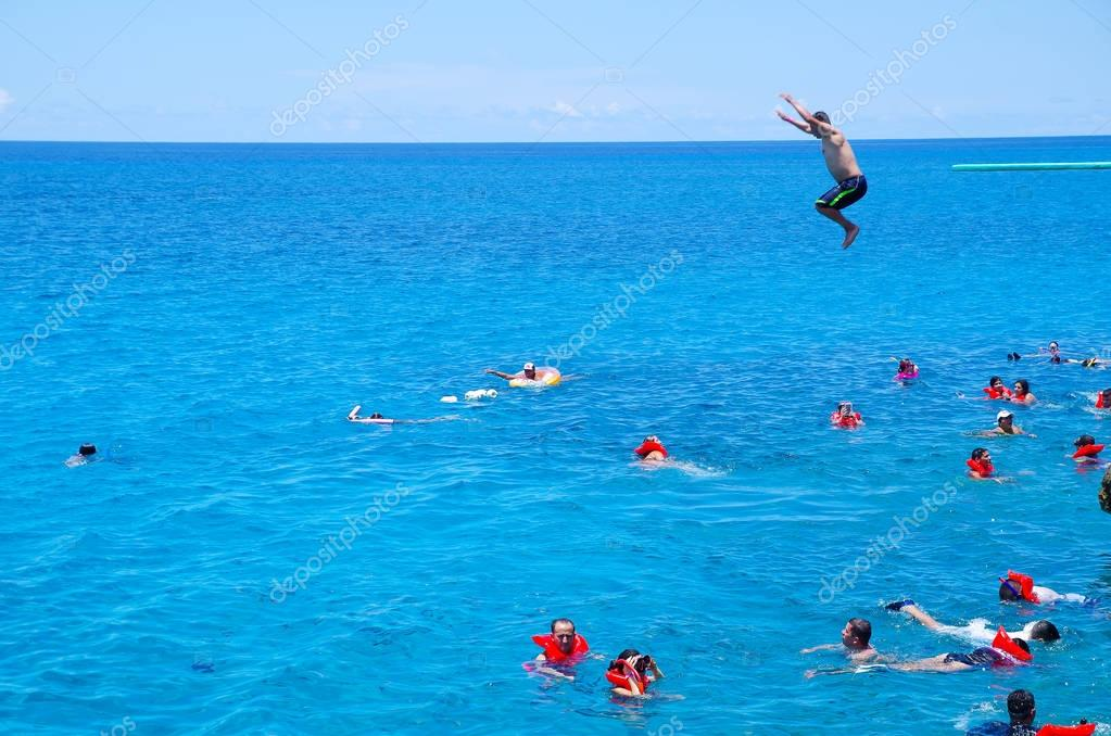 WEST VIEW, COLOMBIA - OCTOBER 03, 2017: Unidentified people jumping, swimming and enjoying the beautiful view in a gorgeous blue water, San Andres Island from Johnny Cay during a sunny day in San