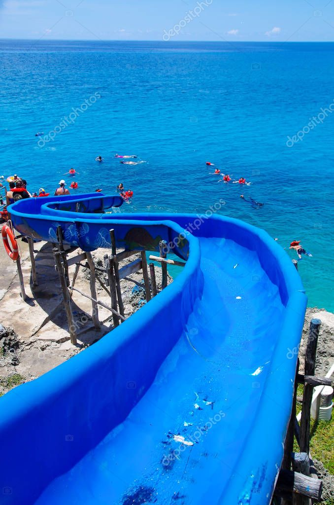 WEST VIEW, COLOMBIA - OCTOBER 03, 2017: Close up of a blue toboggan, with some people swimming and enjoying the beautiful blue water of San Andres Island from west view during a sunny day in San