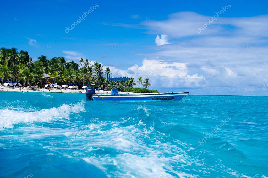 SAN ANDRES, COLOMBIA - OCTOBER 21, 2017: Amazing beautiful view of a man sailing in a boat in an gorgeos blue water, San Andres Island during a sunny day in San Andres, Colombia