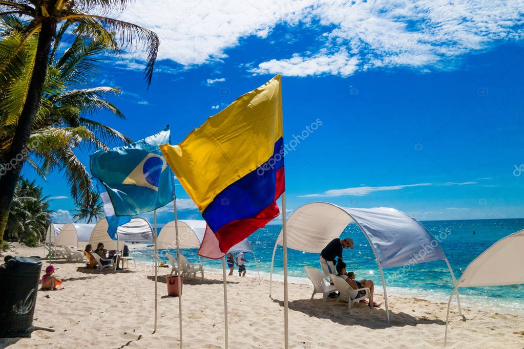 JOHNNY CAY, COLOMBIA - OCTOBER 21, 2017: Unidentified people sitting a chair in the beach and enjoying the beautiful sunny day in the coast of Johnny Cay island with some flags waving with the air
