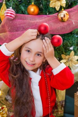 Close up of smiling girl wearing a red santa costume and holding two christmas balls in her hands and posing over her head, with a Christmas tree behind, christmas concept