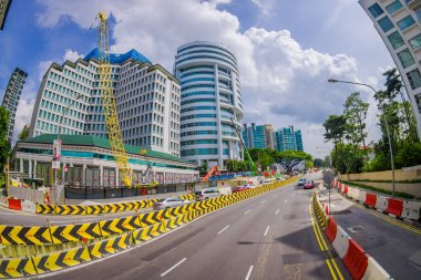SINGAPORE, SINGAPORE - JANUARY 30. 2018: Outdoor view of many cars circulating close to remodeling area a in the streets and Urban scene in the central district of Singapore, fish eye effect