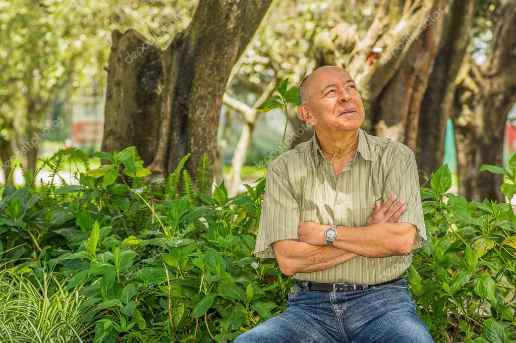 Outdoor view of old man sits on bench, enjoying the nature and having a good rest. All problems left behind
