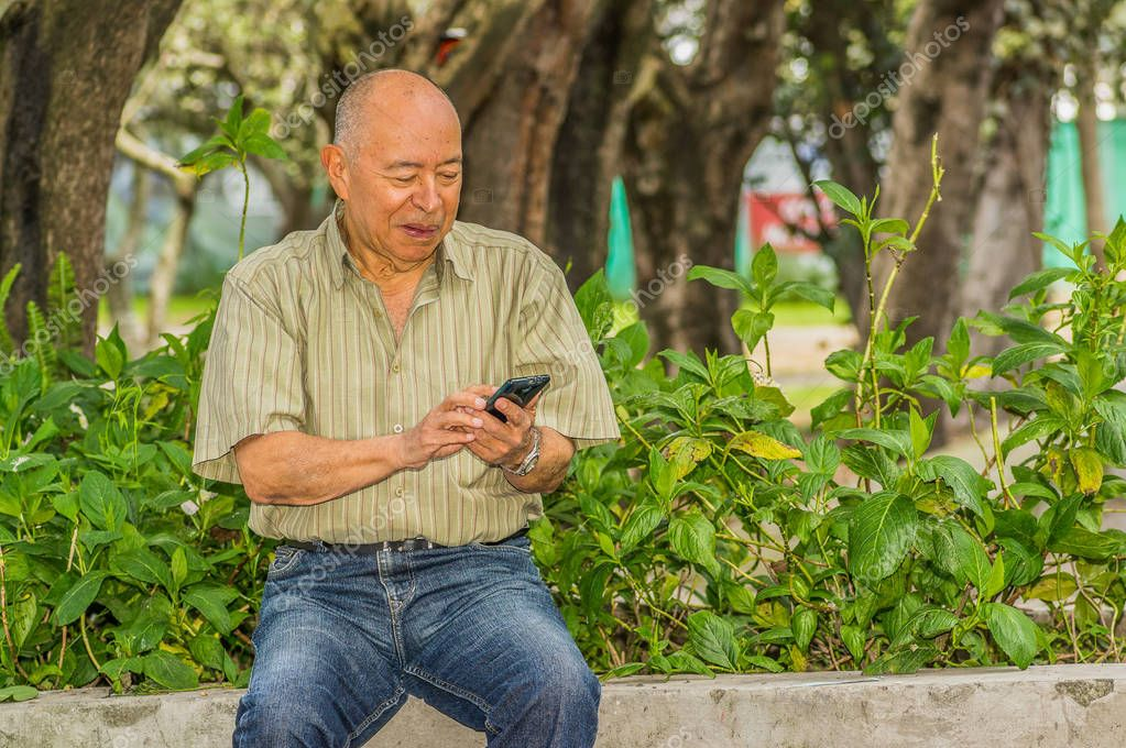 Outdoor view of old man sits on bench with a cellphone in his hand and enjoying the nature and having a good rest. All problems left behind