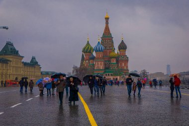 MOSCOW, RUSSIA- APRIL, 29, 2018: Outdoor view of unidentified people walking on Red Square with a gorgeous view of Cathedral of Vasily the Blessed in a rainny day in the city of Moscow