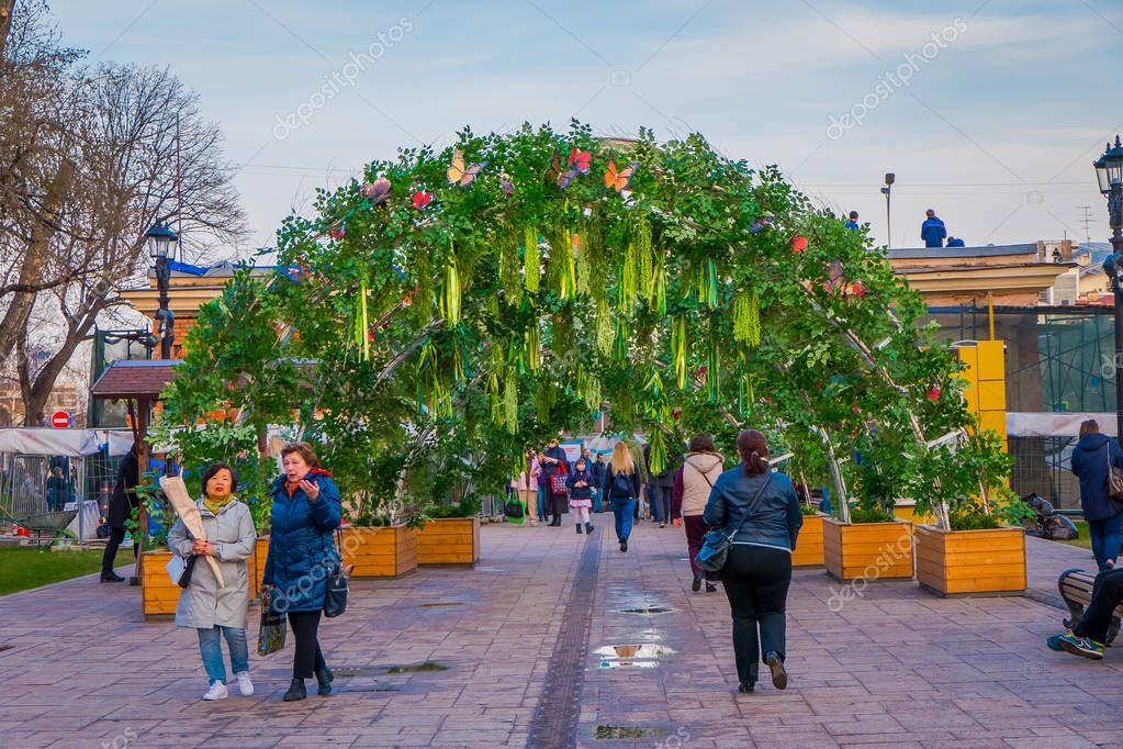 MOSCOW, RUSSIA- APRIL, 29, 2018: Outdoor view of unidentified people walking under a arch made of plants and flower hanging from a metallic struture in a boulevard in the city of Moscow