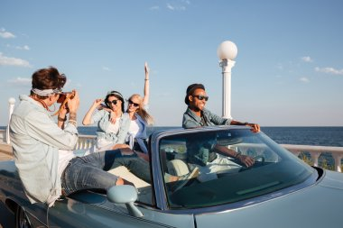 Cheerful young people driving a car and talking photos