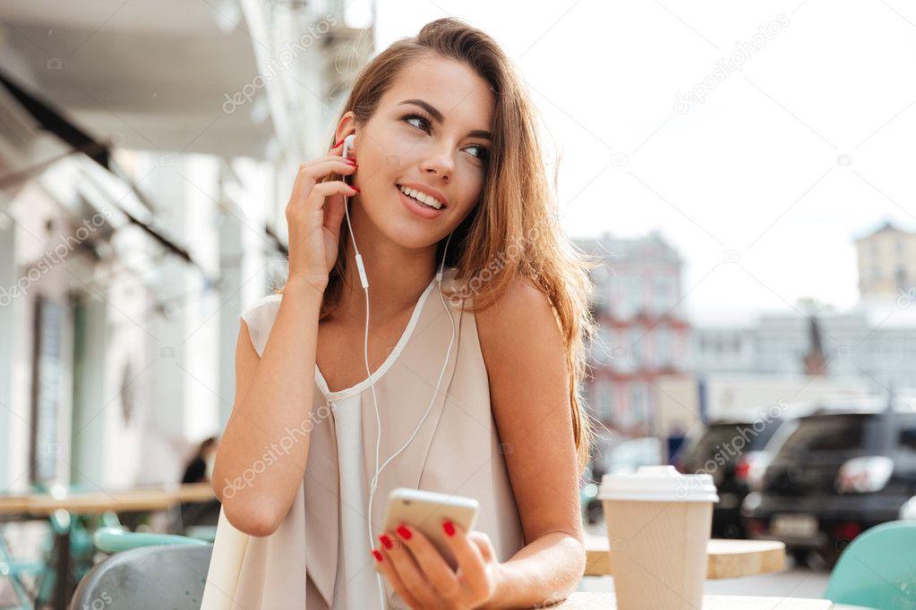 Nő-val fülhallgató hallgatni zene és gazdaság smartphone kávézóban ... 27ce4c2779