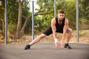 Attractive young male athlete stretching his legs