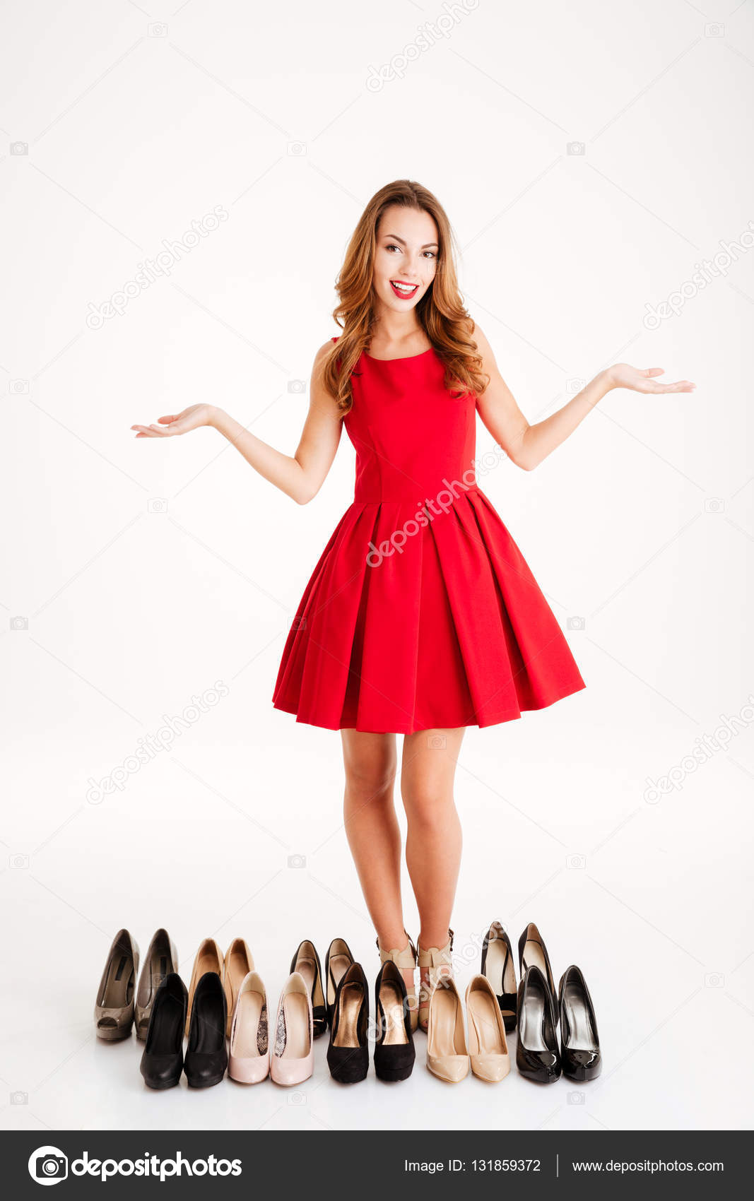 smiling woman in red dress choosing pairs of shoes stock. Black Bedroom Furniture Sets. Home Design Ideas