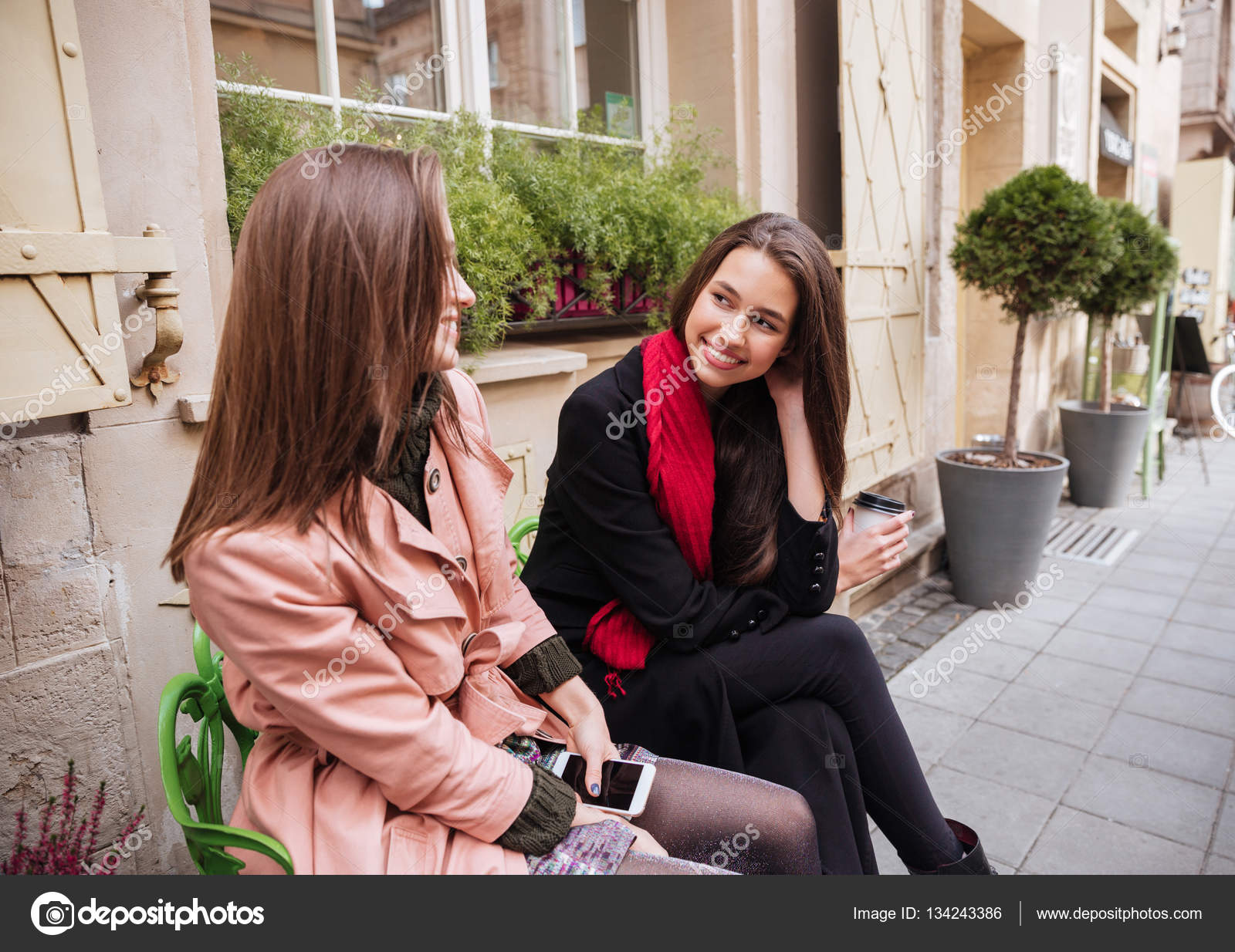 4895afd5b Pretty girls in coats are sitting — Stock Photo © Vadymvdrobot ...