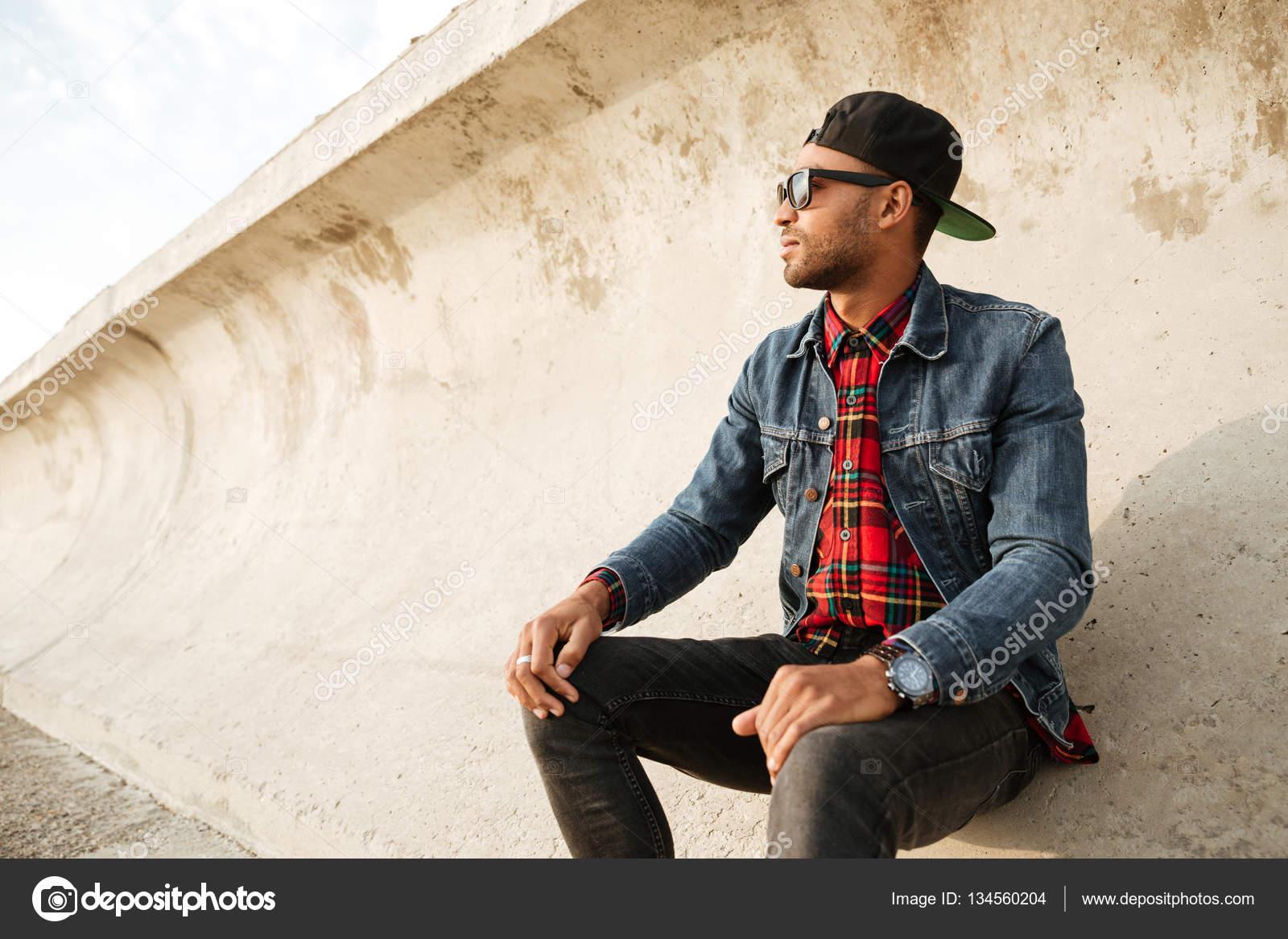Foto de hombre guapo usar gorra y anteojos caminando por la playa. Mirando  a un lado - imágenes  hombres con gorra — Foto de Vadymvdrobot — Foto de ... 7777ab716a1
