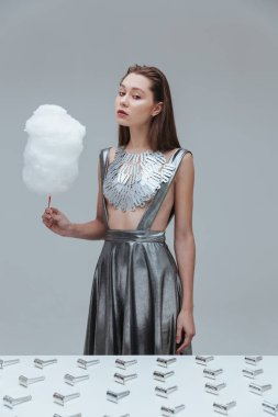 Beautiful woman in top made of blades holding cotton candy