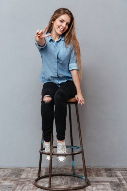 Full length image of Woman in shirt sitting on chair