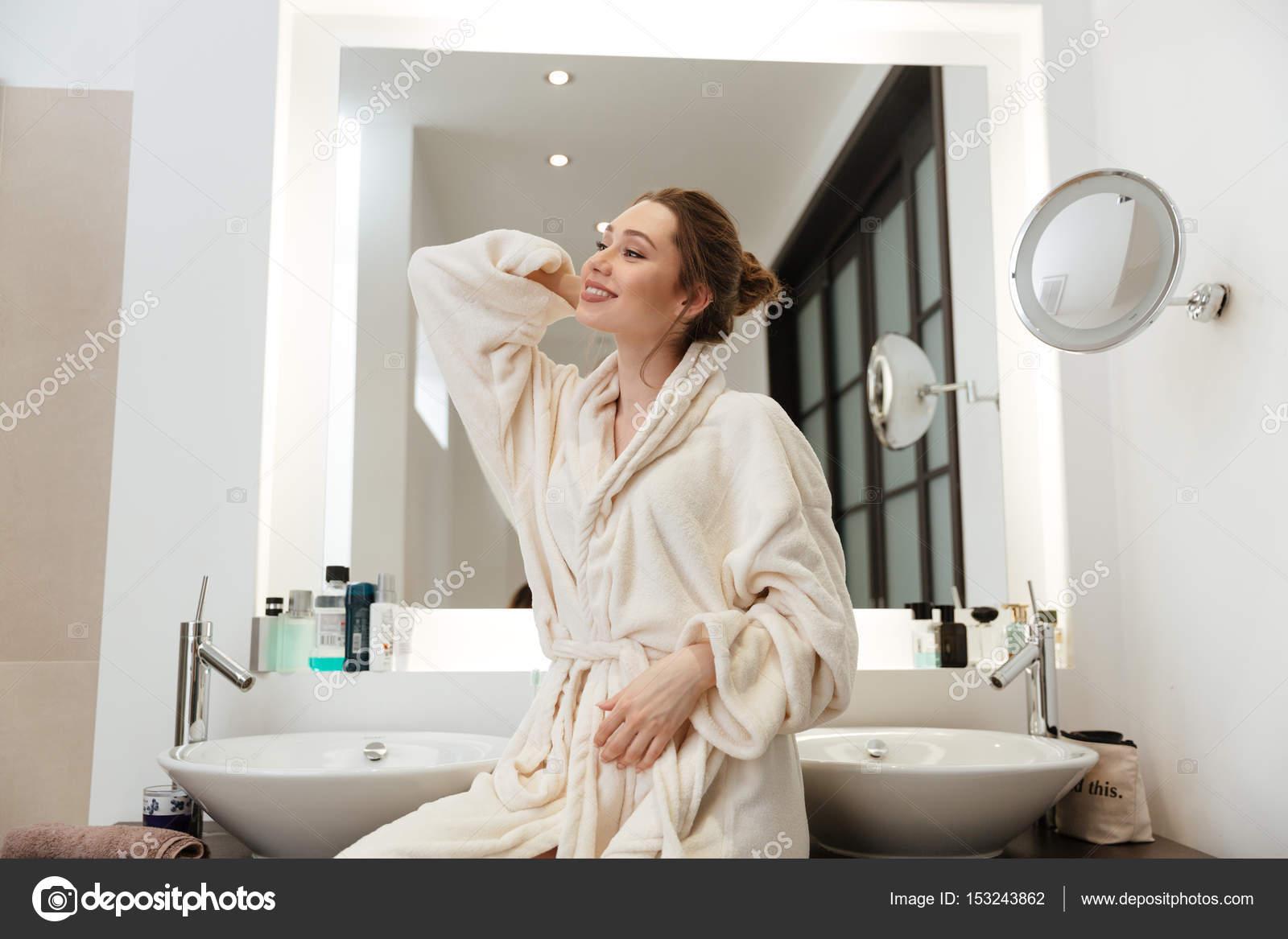 Felice attraente giovane donna in piedi di accappatoio in for Piani di casa 1000 piedi quadrati o meno