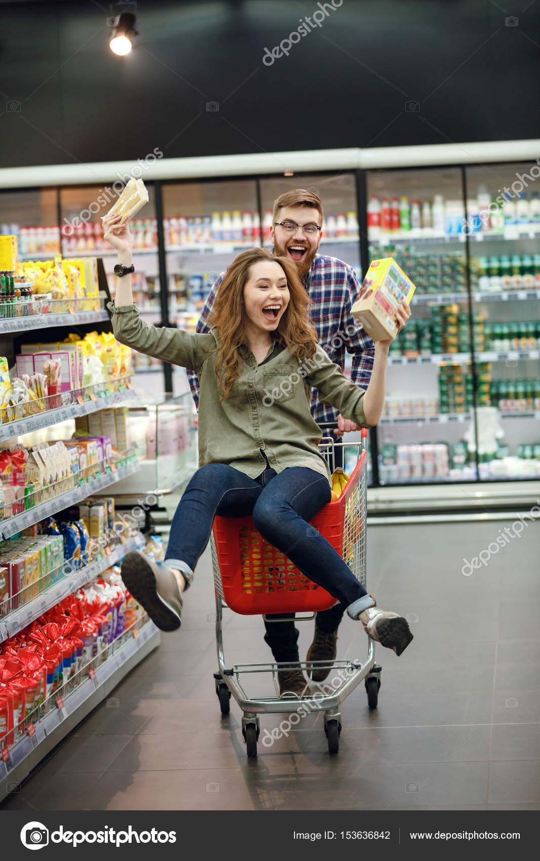 Couple Having Fun With The Shopping Cart In The Supermarket
