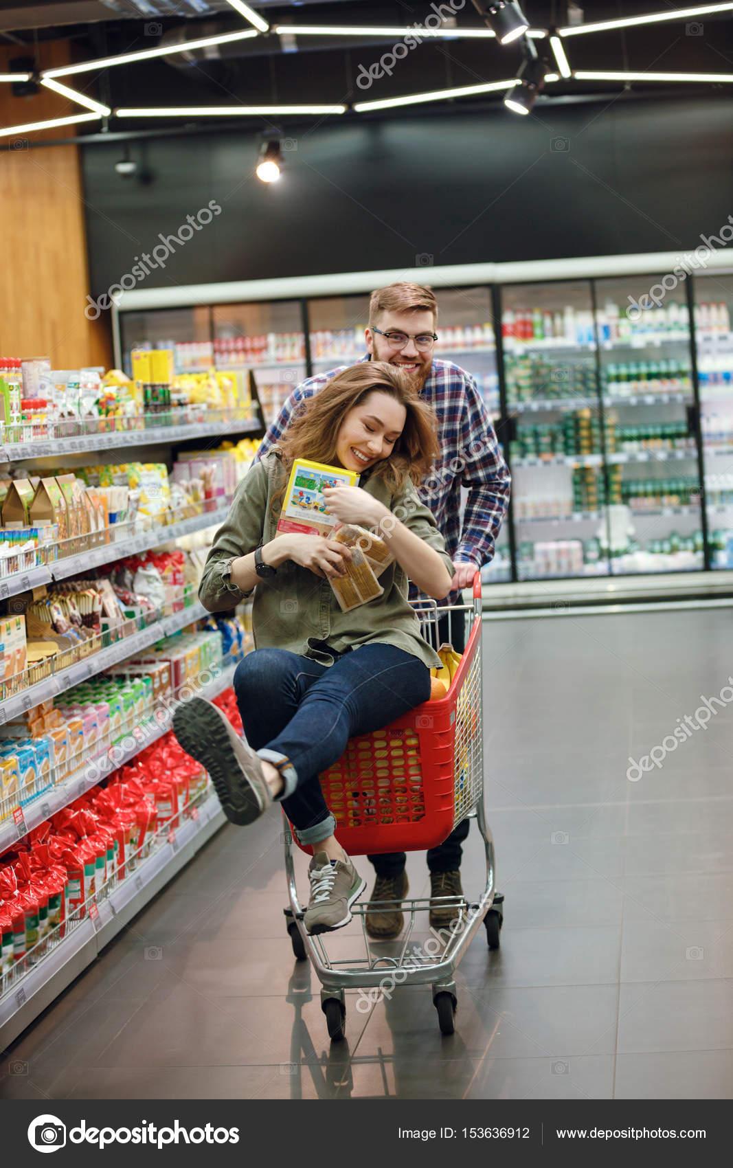 a7a3531fb0 Casal jovem feliz se divertindo com o carrinho de compras ao escolher a  comida no supermercado — Foto de ...
