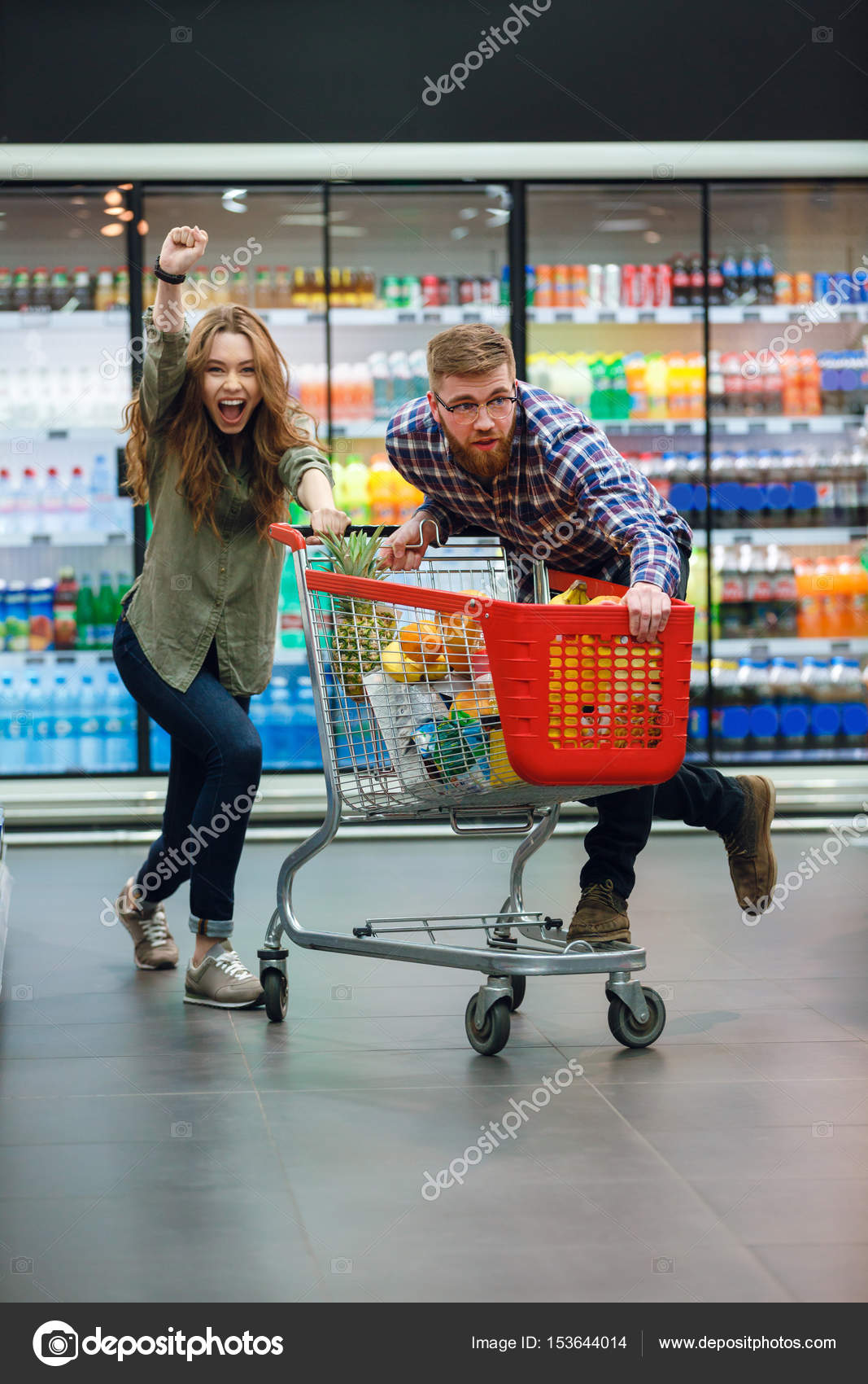 07890e3de7 Casal alegre, se divertindo com o carrinho de compras ao escolher a comida  no supermercado — Foto de ...