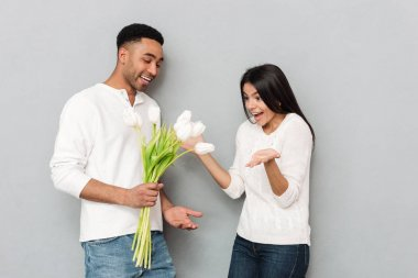 Happy young loving couple standing over grey wall