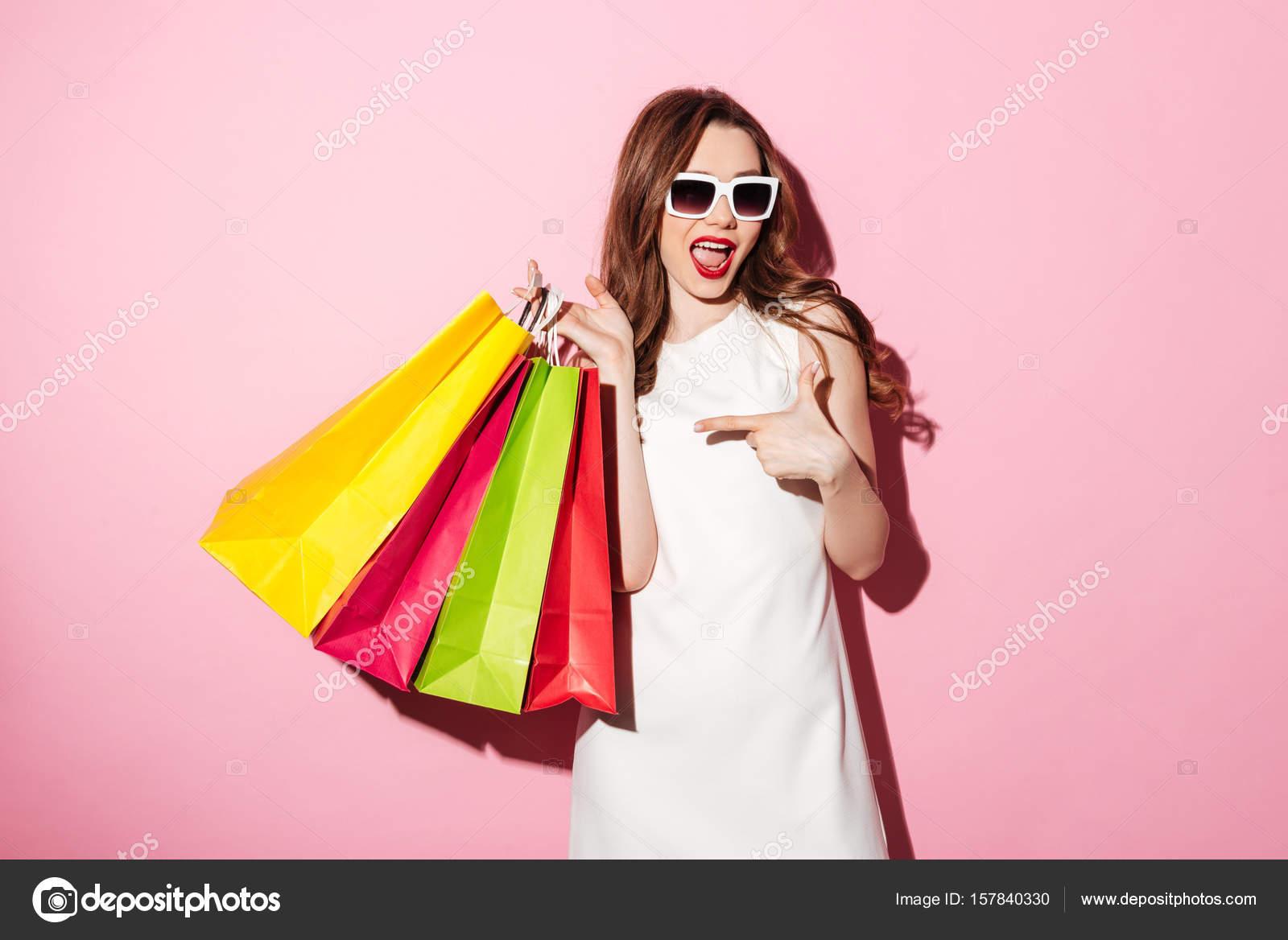 Impresionante joven morena con bolsas señalando — Foto de stock ...