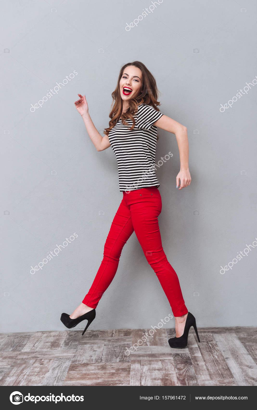 Retrato de longitud completa de una mujer feliz en estudio caminando y  mirando a la cámara sobre fondo gris. Vista lateral. Vertical de la imagen  — Foto de ... da4d7647e12a