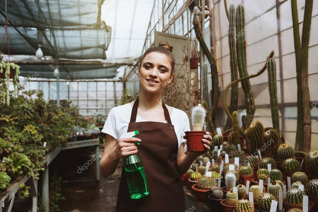 Happy young woman standing in greenhouse near plants
