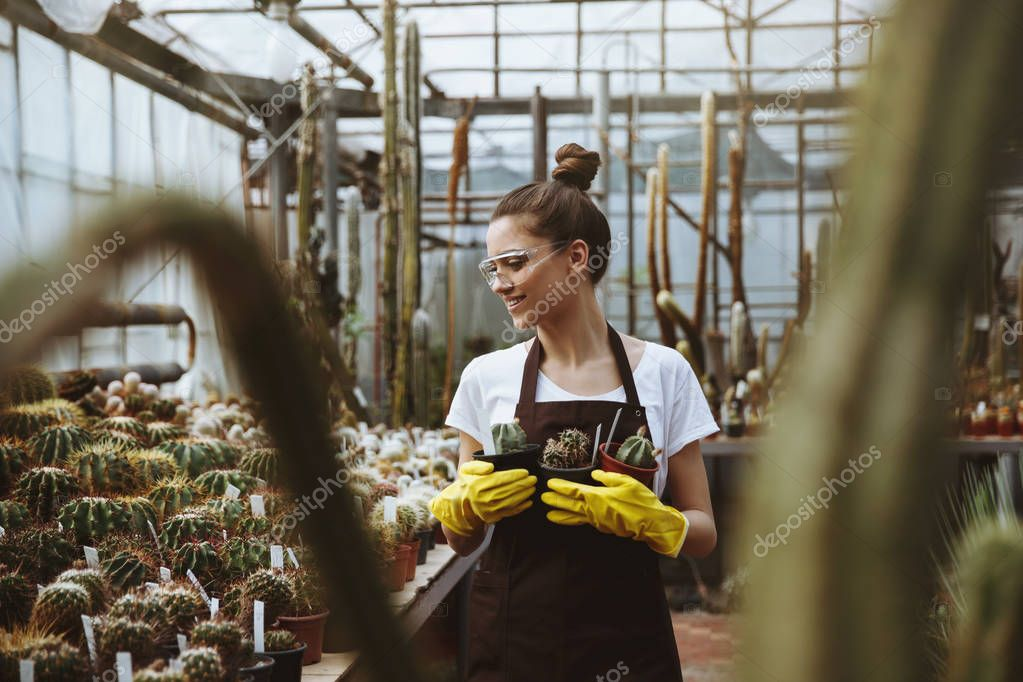 Happy young lady in glasses standing in greenhouse near plants.