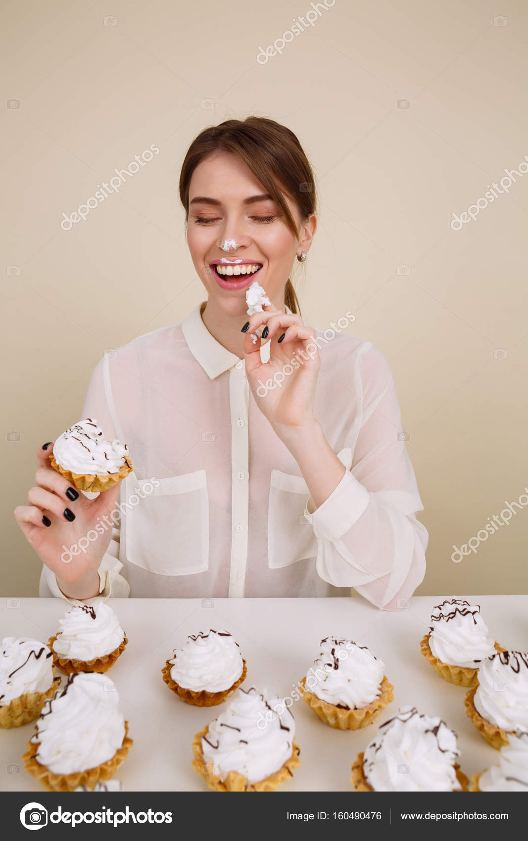 happy woman eating cupcakes at the table and having fun stock photo 160490476 - Woman Decorating Cupcakes