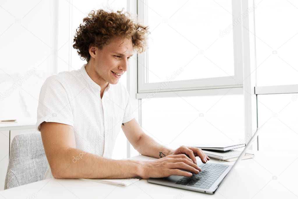 Happy man sitting at the table near window using laptop