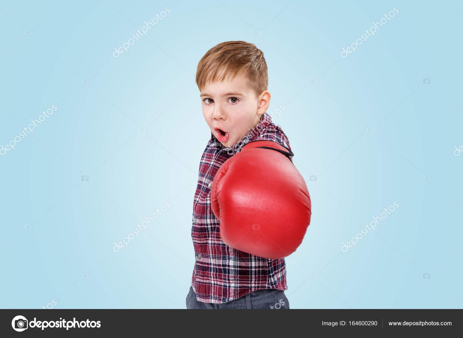 Böse kleine junge mit roten boxhandschuhe stanzen in die kamera