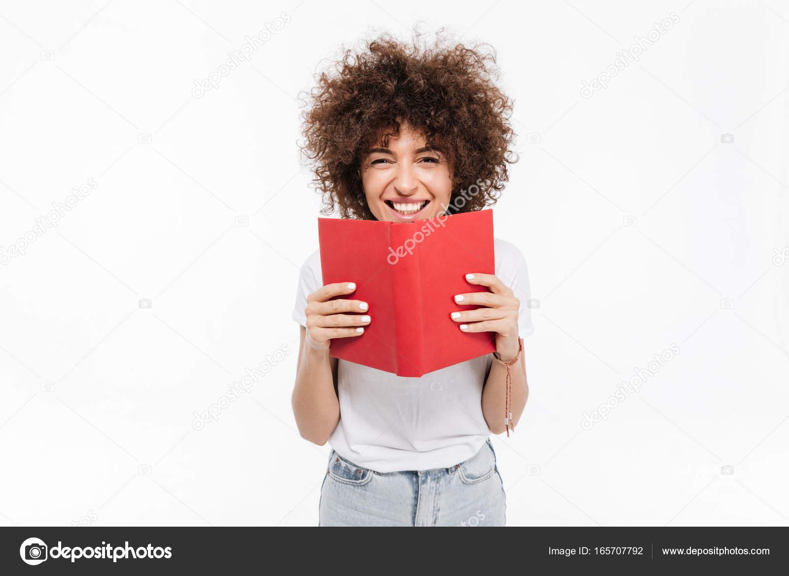 1cd7bb599 Chica alegre feliz con el libro abierto de la tenencia de pelo rizado y  mirando a cámara aislada sobre fondo blanco — Foto de Vadymvdrobot