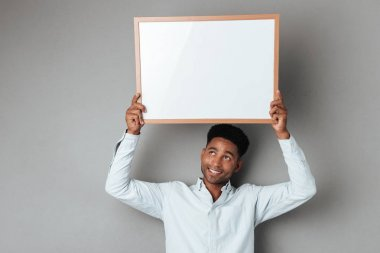 Smiling young african man holding blank board above his head