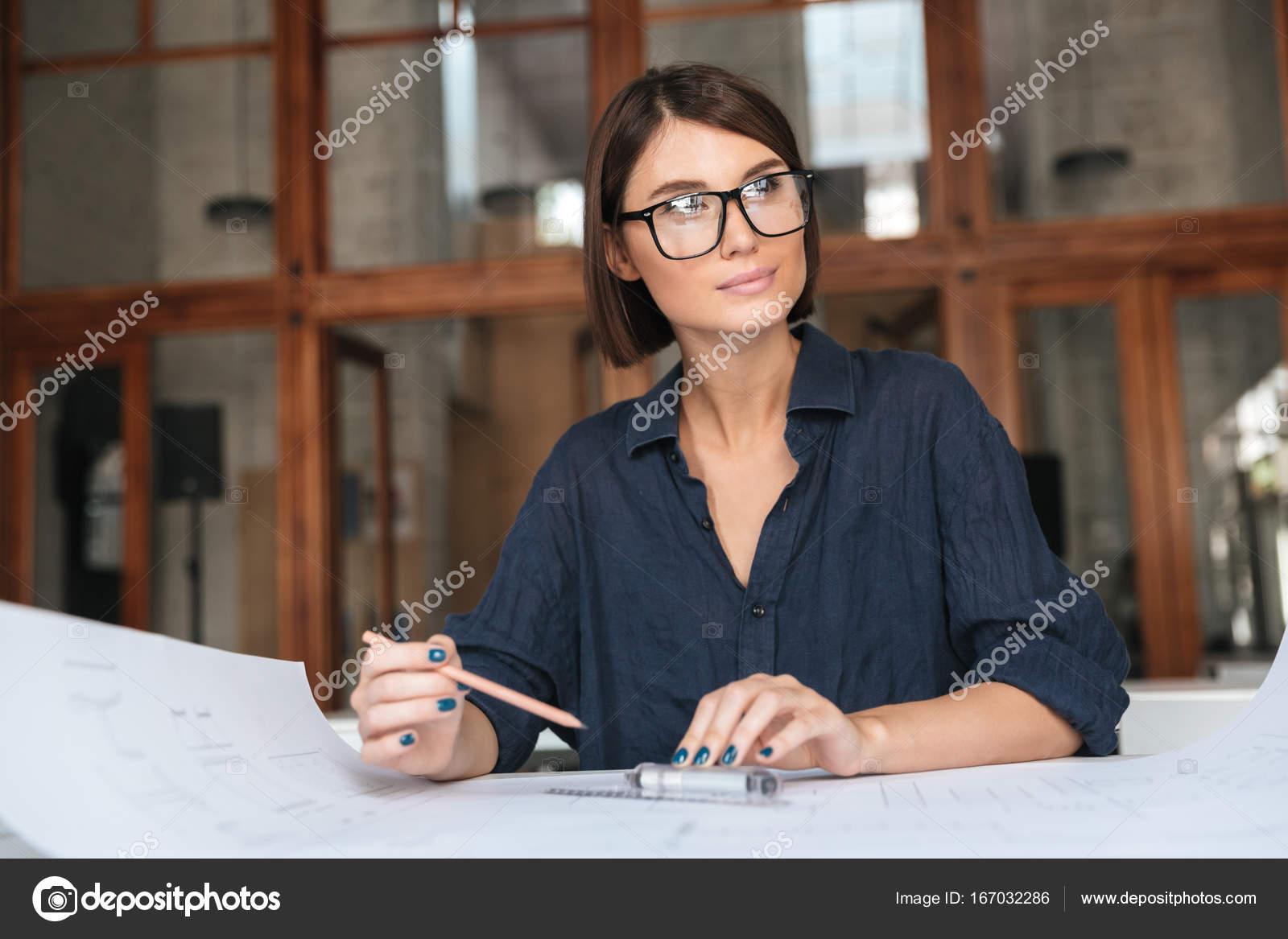 0a6d3426e4 Mujer de negocios pensativo en anteojos sentado en la mesa en la oficina de  trabajo de co y mirando lejos — Foto de ...