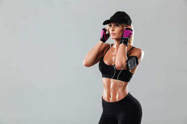 Gorgeous young sports lady standing listening music