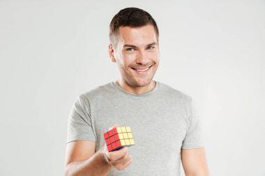 Happy man holding Rubik's cube.
